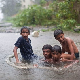 Boys play inside a drain as it rains in Mumbai